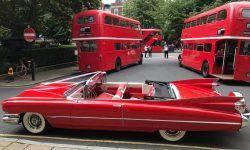 1959 Cadillac convertible in Festival Red (with Routemaster buses)
